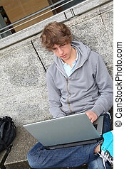 Student with laptop computer outside school building