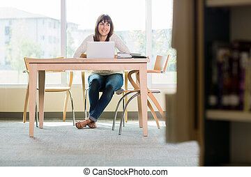Student With Laptop Looking Away In Library