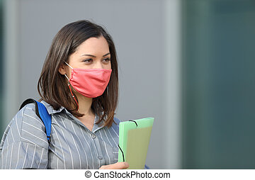 Student with mask walking in the street