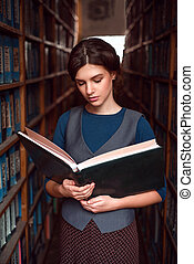 Student with open book  in college library.