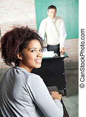 Student With Professor Standing In Background At Classroom