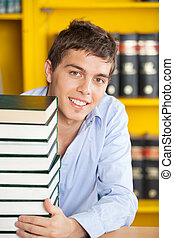 Student With Stacked Books Smiling At Table In Library