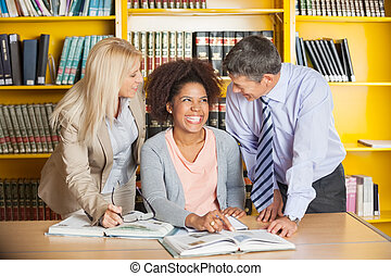 Student With Teachers In University Library