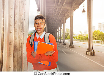 Student with textbook strolling on Paris streets