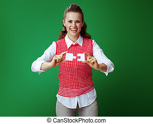 student woman assemble 2 pieces of puzzle on green background