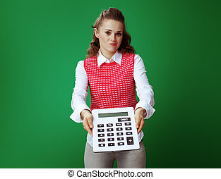 student woman giving big white calculator isolated on green