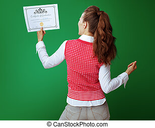 student woman rejoicing looking at Certificate of Graduation