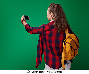 student woman taking photo with phone on green background