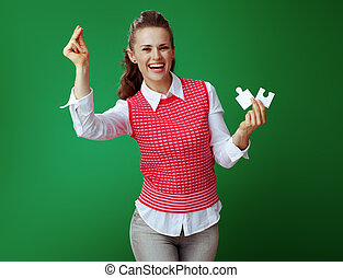 student woman with 2 pieces of the puzzle with fingers clicking