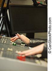 Student working on sound desk adjusting levels in the studio