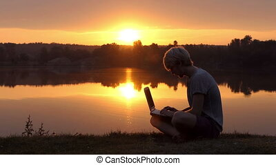 Student working with laptop at sunset.