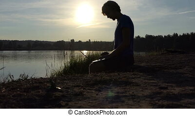 Student works with his laptop on a lake bank in slo-mo