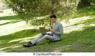 student works with laptop and eats ice cream in a warm day