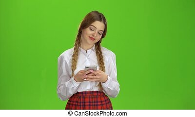 Student writes a message on the smartphone. Green screen -...