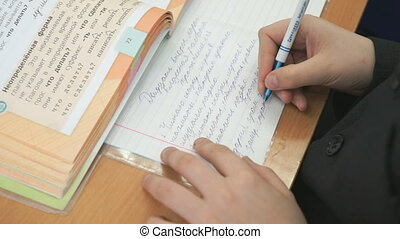 Student writes in a workbook with a ballpoint pen - The...