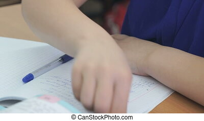 Student writes in a workbook with a ballpoint pen