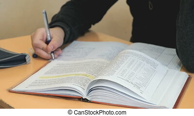 Student writes the text in a copybook on a lesson
