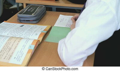 Student writes the text in a copybook using a pen - The...