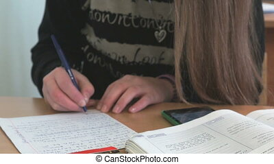 Student writes the text on a white sheet of paper