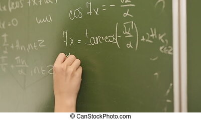 Student writing mathematical formula on blackboard