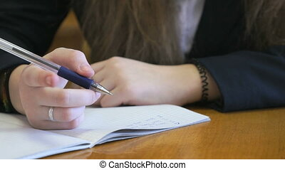 Student dressed in a black suit sits at a school desk writing text in exercise book using ballpoint pen. Close-up