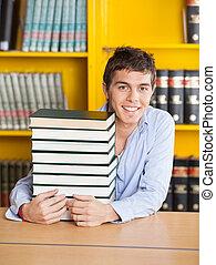 student, zittende , met, opgestapelde, boekjes , in, universiteit, bibliotheek