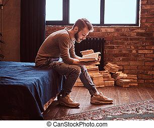 studente, con, elegante, barba, e, capelli, è, preparare, per, esami, sedendo letto, e, lettura, uno, book.