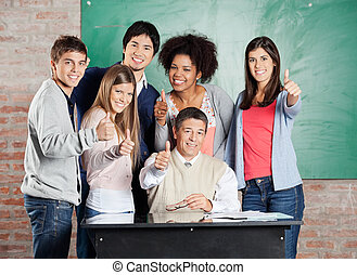 Students And Professor Gesturing Thumb  up At Desk In Classroom