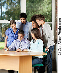 Students And Teacher Looking At Digital Tablet In Classroom
