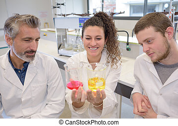 students and teacher to stir something in a glass flask