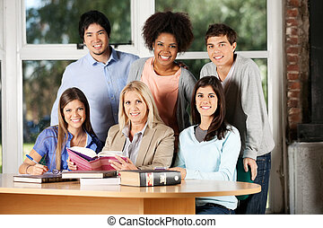 Students And Teacher With Books Smiling In Classroom