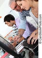 students and teacher working with laptop in college