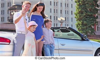 Students and two kids stand near cabriolet at sunny summer day
