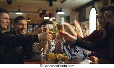 Students are celebrating end of academic session in modern pub. They are toasting, clinking glasses and drinking alcoholic drinks. Young people are having fun.