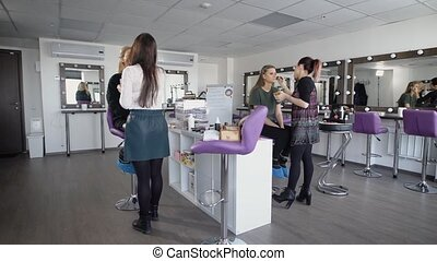 Students at the makeup artist. Two girlfriends in beauty shop. Makeup artists train two girls to final at university. The studio is very cozy, violet convenient chairs.