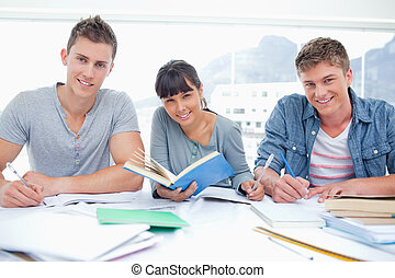Students doing work together as they all look into the camera