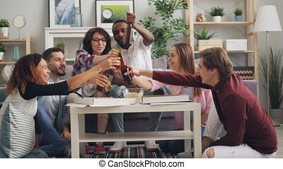 Students eating toasting and drinking at party in house...