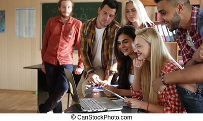 Students excited watching video using tablet computer and laptop university