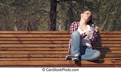 Students girl in casual clothing drinking water - Young...
