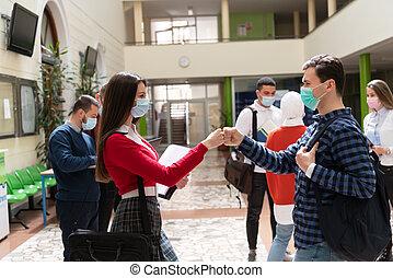students greeting new normal coronavirus handshake and elbow bumping