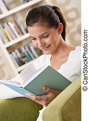 Students - Happy teenager with book sitting on armchair