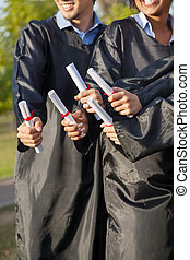 Students Holding Diplomas On Graduation Day In College