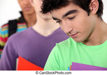 students in a line holding folders