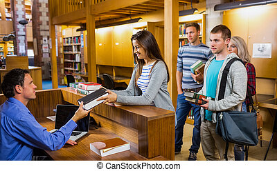 Students in a row at the library counter