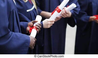 students in bachelor gowns holding diploma scrolls -...