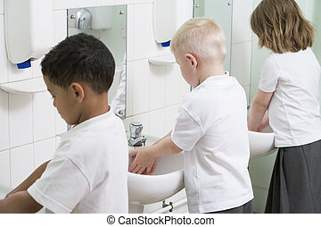 Students in bathroom at sinks washing hands