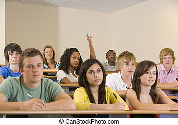 Students in class paying attention and taking notes with one...