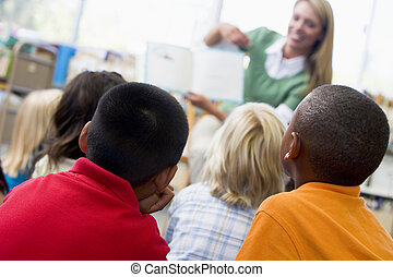 Students in class with teacher reading to them (depth of field)