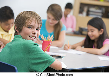 Students in class writing with teacher in background (...