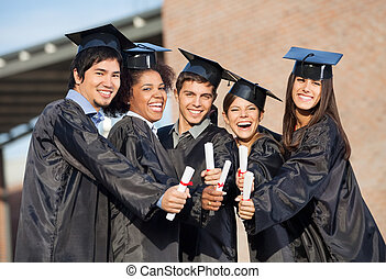Students In Graduation Gowns Showing Diplomas On Campus -...